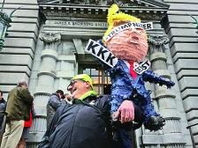 一名示威者手持特朗普紙人玩偶站在上訴法庭門口等待審判結果