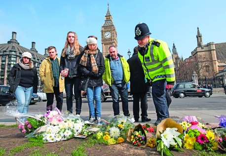 """A police officer looks at flowers laid in tribute with other bystanders in Parliament Square in front of the Houses of Parliament in central London on March 24, 2017 two days after the March 22 terror attack on the British parliament and Westminster Bridge. British police said on March 24 they had made two further """"significant"""" arrests over the Islamist-inspired terror attack on parliament, as they appealed for information about the homegrown killer who left four people dead. Nine people are now in custody over the March 22 rampage in Westminster, in which at least 50 people were injured, 31 requiring hospital treatment, counter-terrorism commander Mark Rowley said. / AFP PHOTO / CHRIS J RATCLIFFE"""